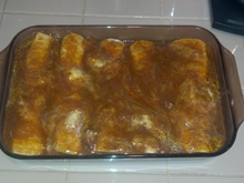 Burritos topped with enchilada sauce and going back in the oven.
